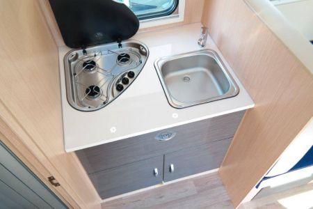 Küche mit einem 140l großen Kühlschrank mit Gefrierfach, Herd und einer Spüle